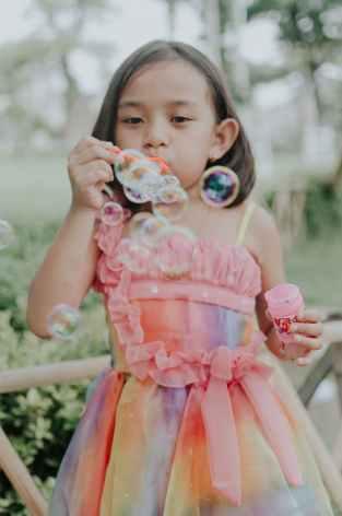 girl wearing multicolored dress making bubbles